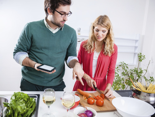 Happy young couple cooking together in kitchen. They are reading the recipe using tablet.